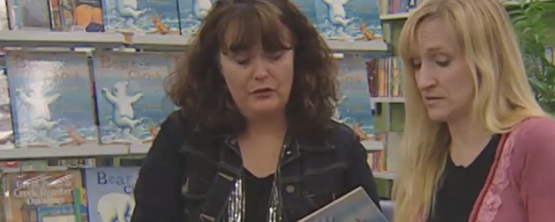 Two women reading a picture book in a library