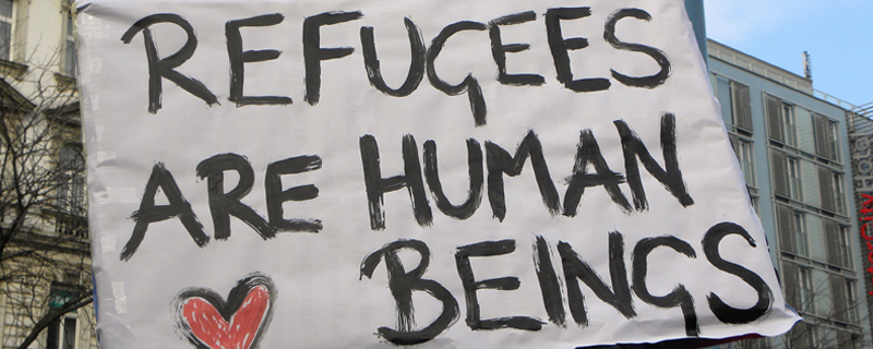 "Hand painted sign that says ""refugees are human beings""."